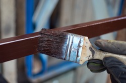 A gloved hand holds a brush. Paint with a crimson paint. Brush close-up. Paint with an iron stick