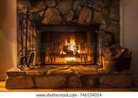 A glowing fire in the stone fireplace to warm a chilly night. - Shutterstock ID 746534014