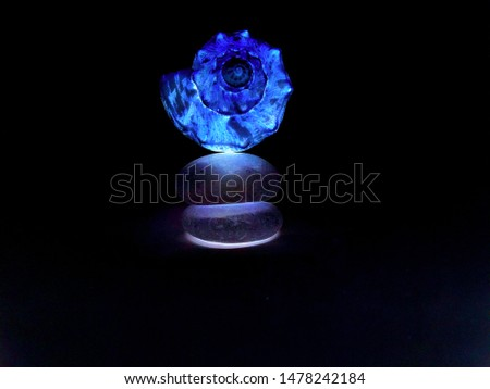 A glowing shell does a perfect balancing act on top of two smooth stones illuminating the dark surrounding.