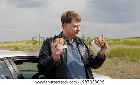 A glutton with two burgers decides which one to eat first. Stock photo ©