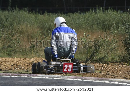A go kart driver getting out of his kart after breaking down