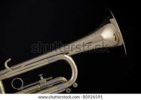 A gold and brass trumpet or cornet isolated against a black background.