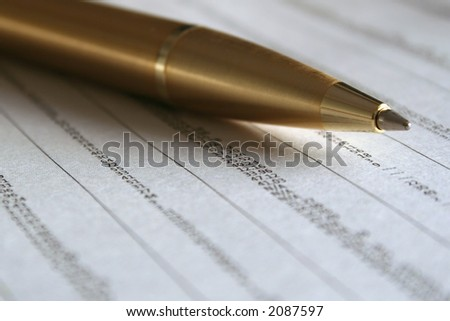 A gold ballpoint pen on the business page of the newspaper.