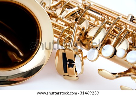 A gold brass saxophone isolated close-up against a white background in the horizontal format.