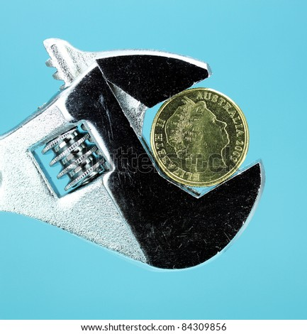 A Gold Dollar Coin in a being squeezed in a silver adjustable spanner, against a light pastel blue background asking the questions how is your household budget?