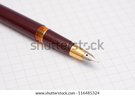A gold-plated pen with a notebook