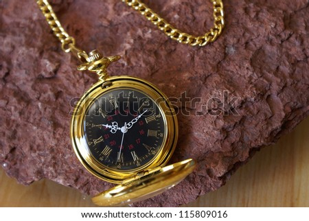A gold pocket watch on a red sandstone.