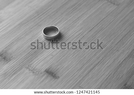 A gold ring on a wooden table top. This image can be used to represent marriage, divorce or commitment.