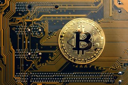 A golden coin with bitcoin symbol on a mainboard.