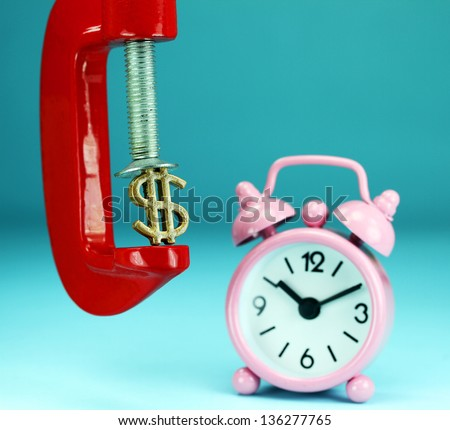A golden Dollar symbol placed in a red clamp with a pastel blue background, with a pink alarm clock in the background indicating the pressure on dollar.