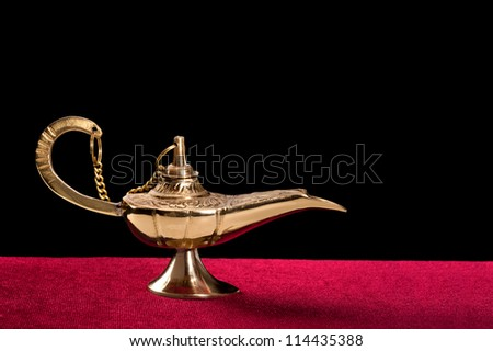 A golden genie lamp on red velvet against a black background. Designers have the option to place any kind of smoke or ghostly image coming out of the lamp.
