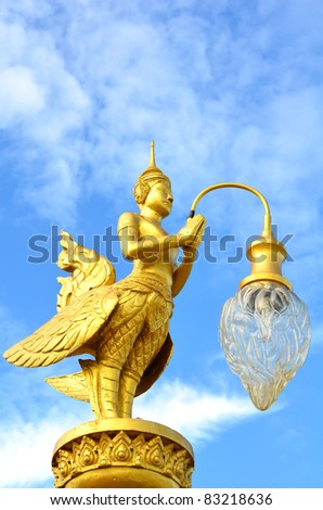 A golden Kinnara (The male counterpart of Kinnari) with lamp. Kinnari are half bird half women creatures in Thai and Lao mytholgy.
