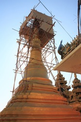 A golden pagoda surrounded by bamboo scaffolding being repaired at Kyaikthanlan Pagoda in Mawlamyine, Myanmar
