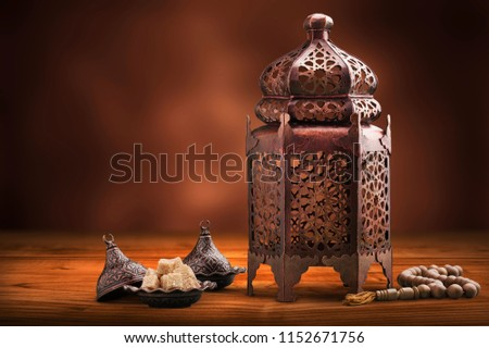 A golden Ramadhan lamp with Islamic rosary #1152671756