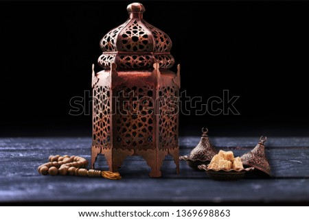 A golden Ramadhan lamp with Islamic rosary #1369698863