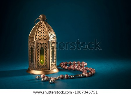 A golden Ramadhan lamp with Islamic rosary beads on dark background. Ramadan - an important Islamic festival. Islamic festive greeting card photo. #1087345751