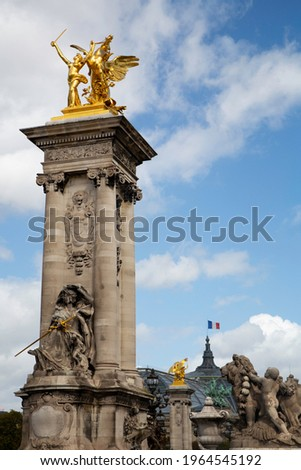 A golden sculpture over a column at the Alexandre III bridge and the national french flag on the Palais Royal rooftop on the background, in Paris, France. Stock photo ©