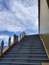 A golden stairway leading to heaven, with beautiful clouded sky and architecture
