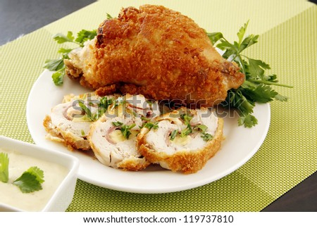 A golden stuffed fried chicken with garnishing