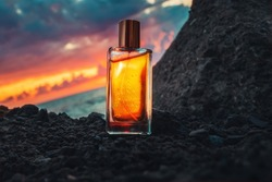 A golden transparent perfume bottle on a stone. Close-up. In the background, the ocean and cloudy sunset. Littered horizon. Concept of International Fragrance Day.
