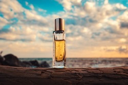 A golden transparent perfume bottle with drops on a log. Close-up. In the background, the ocean and cloudy sunset sky. Bottom view. Concept of International Fragrance Day.