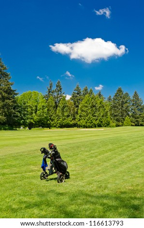 A golf bag on three wheel golf cart over a beautiful green with blue sky and white clouds.