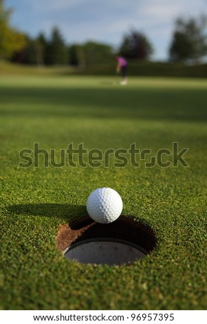 A golf ball captured as it drops into the hole with the golfer in the distance. - stock photo