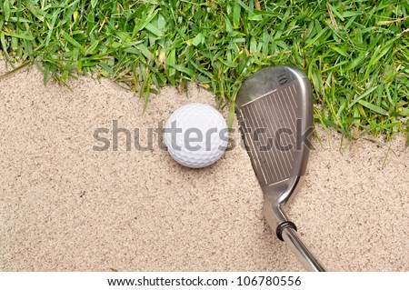 A golf ball in a sand trap getting ready to be hit with an iron.