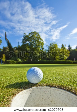A golf ball just as it drops into the cup on a beautiful day
