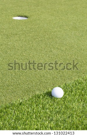 A golf ball near the hole on a green