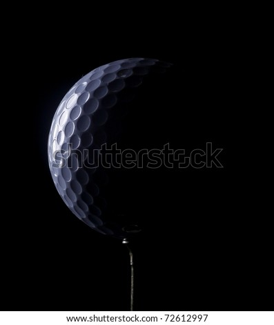 A golf ball on a tee, in dramatic black and white