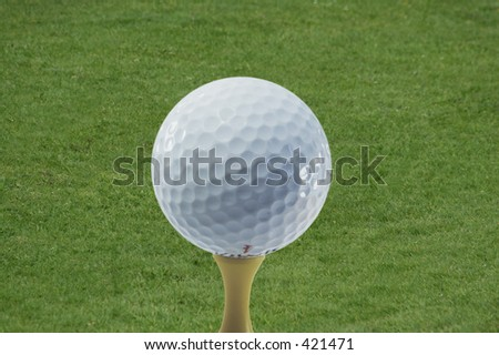 A golf ball on a tee ready to be hit