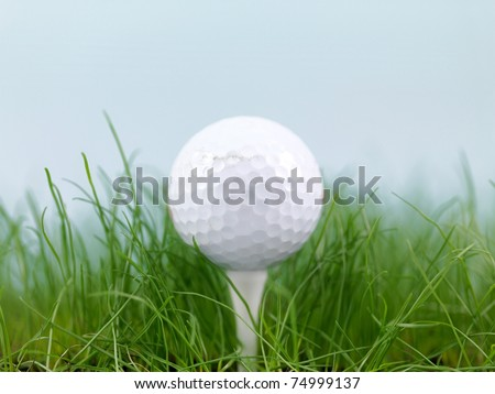 A golf ball on green grass isolated against a blue sky