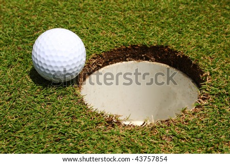 A golf ball on the edge of a hole