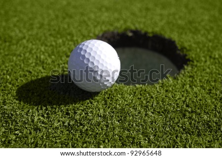 A golf ball sits at the lip of the hole on the putting green.