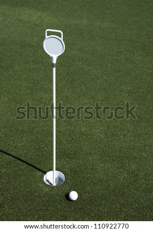 A golf ball sits near the hole on the putting green