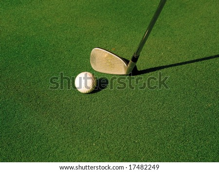 A golf club about to strike a golf ball on a tee