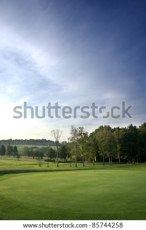 a golf course green with flag at dawn