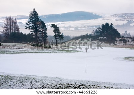 A golf course in Scotland on a snowy winter morning shortly after sunrise.