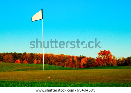 A golf course with a blue sky and autumn colors