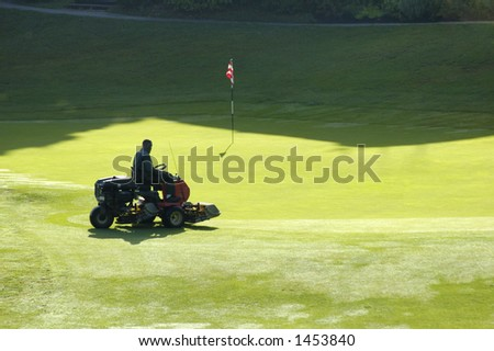 A golf course worker mows the grass of a green, in the early morning.