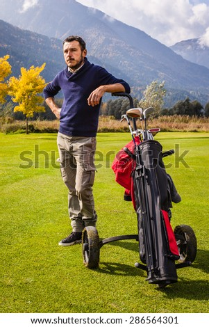 a golf player playing on a beautiful golf course and a golf bag full of golf clubs