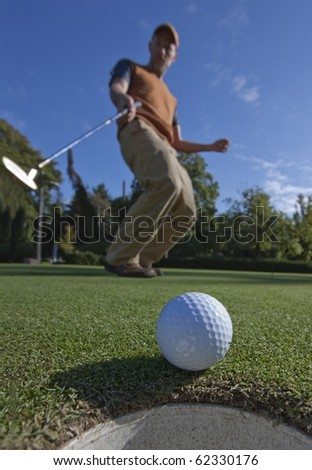 A golfball just as it's about to drop into the cup, golfer in the background arching as it drops