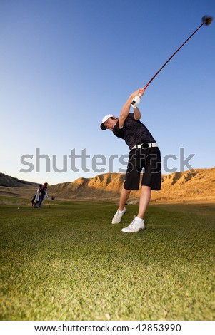 A golfer driving the ball down the fairway