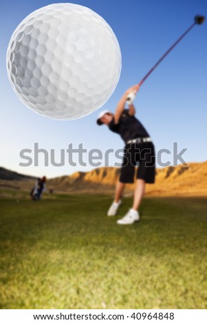 A golfer driving the ball down the fairway focus on the ball
