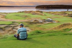 a golfer enjoying the view at sunset
