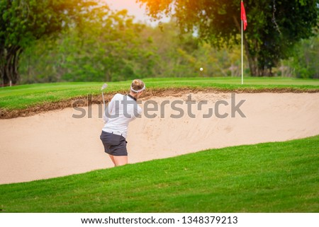 A Golfer is teeing off golf ball by golf club from tee boxes at golf course and sand bunker in golf competition game with sand bunker and fairway background.
