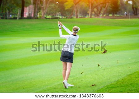 A Golfer is teeing off golf ball by golf club from tee boxes at golf course in competition game with green grass  fairway background.