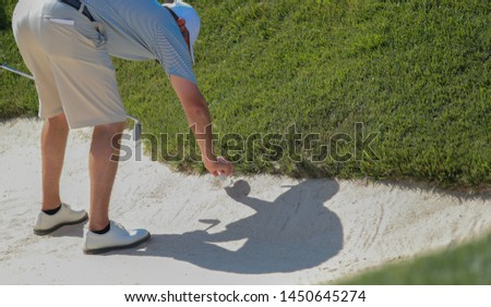 A golfer picks picks up his ball in a bunker to identify it.