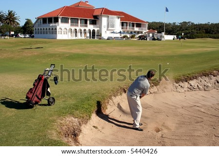 A golfer playing a stroke out of a sand trap with the club house in the background
